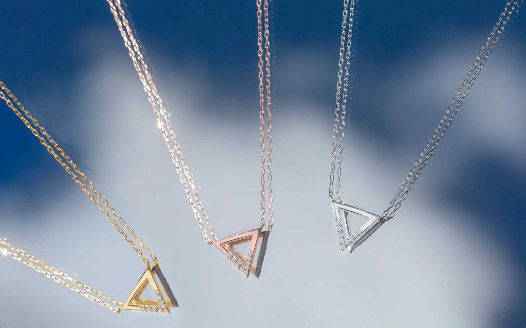 Gargantillas motivo triángulo de oro de 18 Kt y topacios sobre espejo